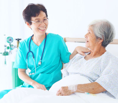 Senior nurse take care elderly woman in room of hospital
