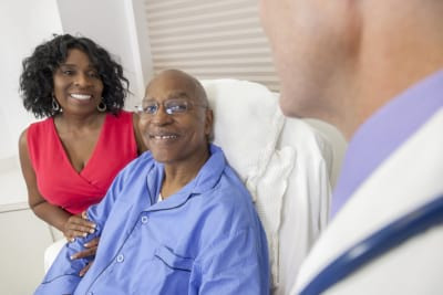 a happy elderly man recovering with in the hospital bed with his wife and male doctor