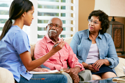 a caregiver having conversation with the two elderly couple
